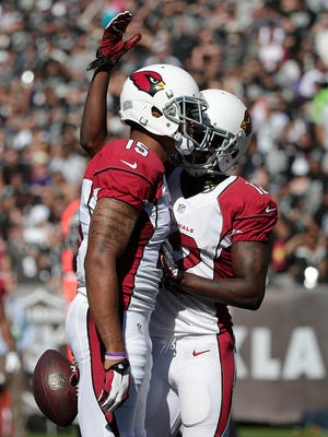 Cardinals wide receiver Michael Floyd (15) celebrates after catching a touchdown pass with wide receiver John Brown during the second quarter of an NFL football game against the Oakland Raiders in Oakland, Calif., Sunday, Oct. 19, 2014. The Cardinals won 24-13.