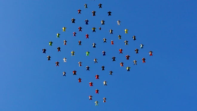 This photo taken, Oct. 17, 2015, and provided by Skydive Perris shows 61 wingsuit skydivers setting a new world record for the largest aerial formation in the sky over Perris, Calif., about 70 miles southeast of Los Angeles. Exiting from three airplanes at 13,5000 feet, flyers formed a diamond shape in flight, covering a distance of more than two miles, before dispersing at 5,500 feet. The record event included participants from 12 countries.(Mark Harris/Skydive Perris via AP)