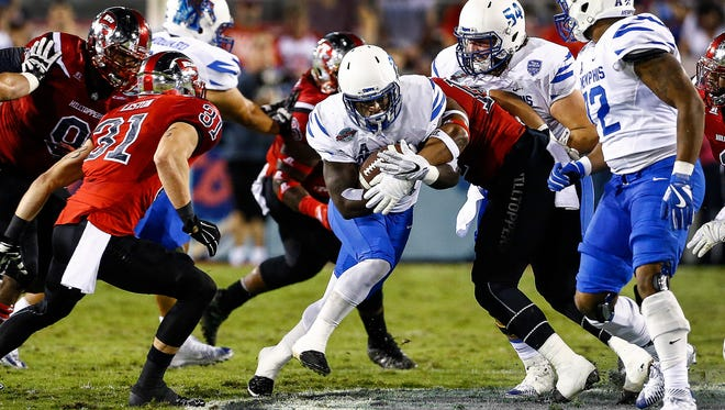 University of Memphis running back Doroland Dorceus (middle) scrambles for positive yards against the Western Kentucky University defense during first quarter action in the Boca Raton Bowl in Florida.