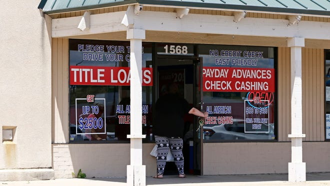 A woman enters an All American Check Cashing location in Brandon, Miss., Friday, May 12, 2017.