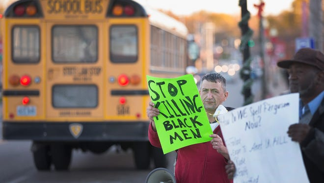 A school bus passes demonstrators protesting outside the police station Nov.10 in Ferguson, Mo.