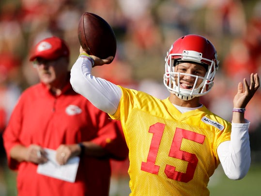 Kansas City Chiefs quarterback Patrick Mahomes (15) throws while head coach Andy Reid looks on during NFL football training camp Saturday, July 29, 2017, in St. Joseph, Mo. (AP Photo/Charlie Riedel)