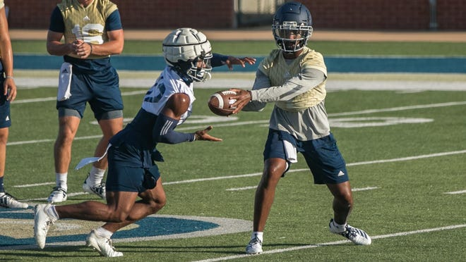 Georgia Southern quarterback Shai Werts, right, hands off to running back Wesley Kennedy III of Savannah during the first football practice of the fall on Friday morning at Paulson Stadium in Statesboro.
