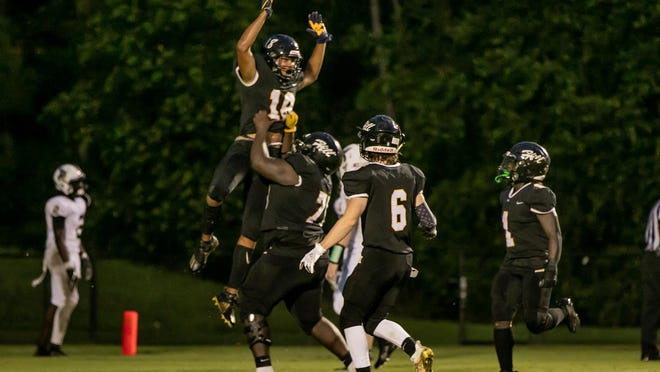 Richmond Hill's Isaiah Allen (18) celebrates with teammates after scoring on a 24-yard touchdown pass from Tyler Coleman during the first quarter of Friday's game against Wayne County at Richmond Hill.