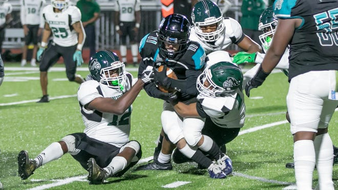 Islands High senior running back Abdul Lara (11) is brought down by Windsor Forest's DeMarquez London (12) and Jason Snowdon (14) early in Friday's game at Islands Stadium.