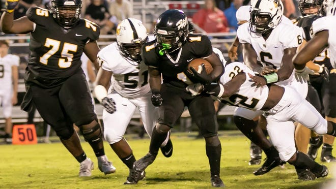 Richmond Hill's Ashaud Roberson (1) gains yardage up the middle against the Wayne County defense early in a Sept. 18 game at Richmond Hill. The host Wildcats won 24-21.