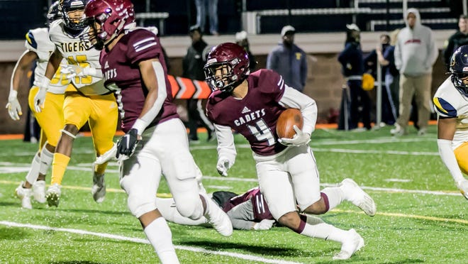 Benedictine's Justin Thomas (4) follows blocking from senior Leshon Brooks Jr. (7) during the GHSA Class 4A first-round state playoff game against Troup County on Saturday night at Memorial Stadium.