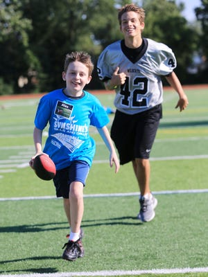 Sunshine's camper Alex Banko outraces his buddy, Plymouth football player Jonah Brafford.
