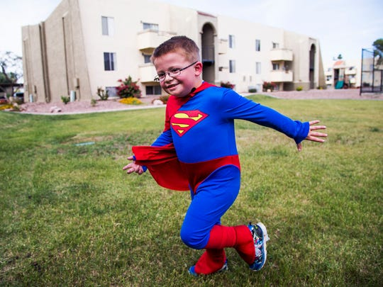 "Dylan Marshall, 5, ""flies"" in his Superman costume"