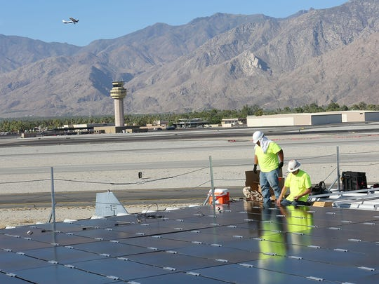Workers with Tiger Electric install solar panels on