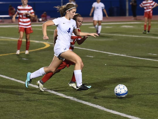 Spring Grove's Catherine Swiger, left, runs the ball