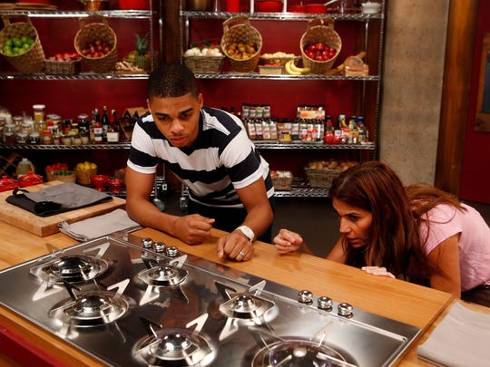 Recruits Lawrence Crawford, of Deptford, and competitor Glenda Galeano try to turn on a stove as seen on Food Network's Worst Cooks in America, Season 8.