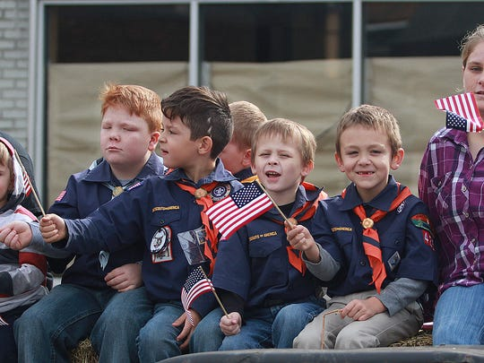 Gallatin Boy Scouts waves as they ride in the Gallatin