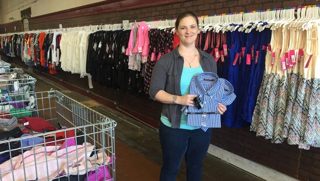 Manager Jennifer Kindred shows off some of the merchandise at the Gimme a $5 clothing store in Lebanon.