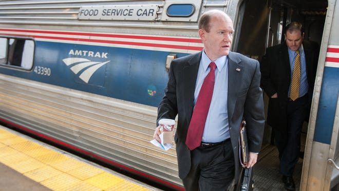 U.S. Sen. Chris Coons, followed by his state press secretary Brian Cunningham, walks off an Amtrak train in New Carrolton, Maryland, as he heads to an energy conference at the Gaylord National Resort and Conference Center at the National Harbor on Tuesday morning, Feb. 25, 2014.