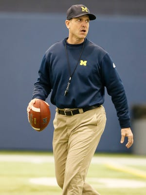 Michigan head coach Jim Harbaugh overseeing the offensive during football practice on Thursday, March 19, 2015 in Ann Arbor.