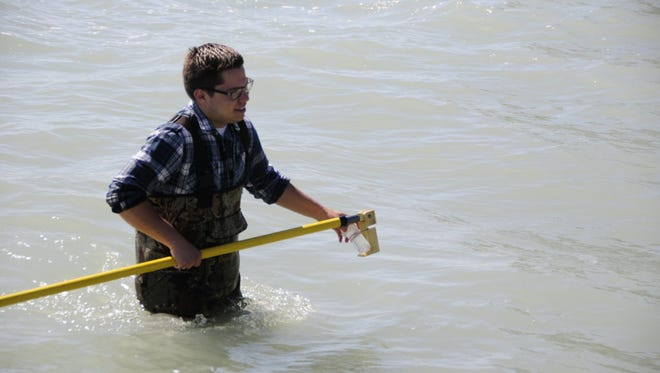 Adam Czubachowski finishes collecting a water sample for testing at Holland Road Beach in Port Huron.