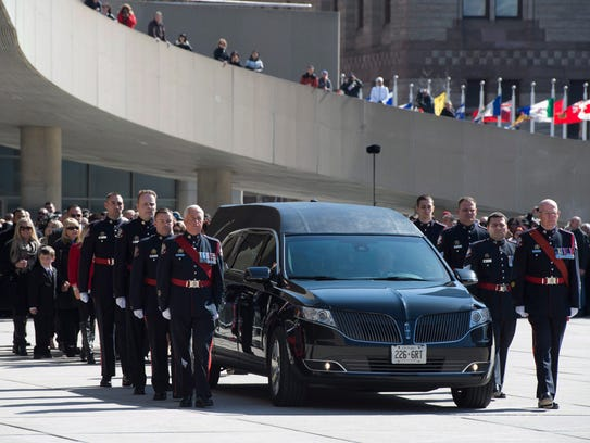An honor guard escorts the hearse carrying the casket