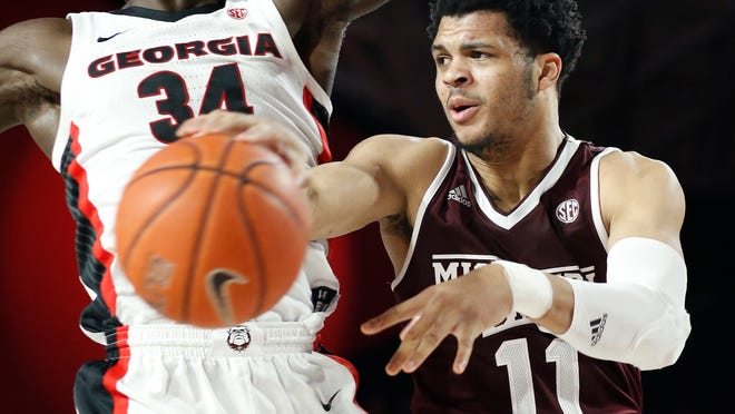 Mississippi State guard Quinndary Weatherspoon (11) throws a pass around Georgia forward Derek Ogbeide (34)during an NCAA college basketball game in Athens, Ga., Wednesday, Feb. 20, 2019. (Joshua L. Jones/Athens Banner-Herald via AP)