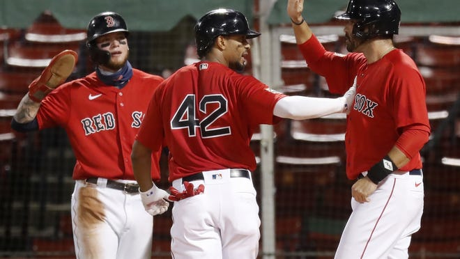 Red Sox shortstop Xander Bogaerts (center) celebrates his three-run home run that also drove in Alex Verdugo (left) and J.D. Martinez during the first inning of a baseball game against the Washington Nationals, Saturday, Aug. 29, 2020, in Boston.