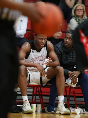 Aspire Academy's Charles Bassey (23) sits next to guardian Hennssy Auriantal on the sideline during a game against Orangeville Prep at Seneca High School.   Feb. 9, 2018