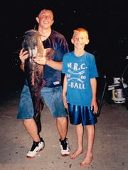 "Dale Uthoff Jr., left, and Jarrod, right, went out one summer night on the Iowa River and caught a 50-pound flathead catfish, well after their parents were asleep. But of course they had to break the news – so there was mud-covered Dale Jr. with a giant fish draped over his shoulder and young Jarrod, grinning ear to ear. ""Their eyes got as big as saucers,"" Dale Jr. says."