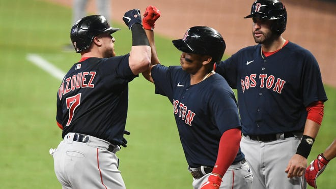 Red Sox catcher Christian Vazquez, left, celebrates after hitting a grand slam against the Atlanta Braves during the second inning at Truist Park on Saturday night.
