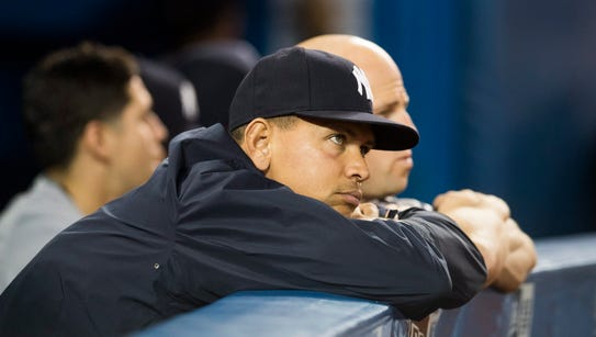New York Yankees' Alex Rodriguez watches from the dugout