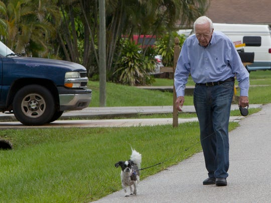 San Carlos Park resident Ira Weis, 90, walks Dorian, his Shih Tzu, after work one day last month. He was a radio operator on board a B-17 during World War II.