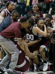 Mississippi State guard Morgan William (2) celebrates with teammates after she hit the winning shot in overtime to defeat Connecticut in an NCAA college basketball game in the semifinals of the women's Final Four, Friday, March 31, 2017, in Dallas. Mississippi State won 66-64. (AP Photo/LM Otero)