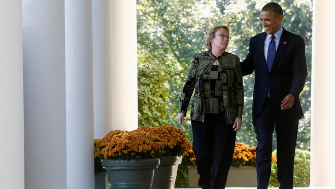President Barack Obama walks from the Oval Office to the Rose Garden of the White House in Washington, Monday, Oct. 21, 2013, with Janice Baker, who runs a small business in Selbyville, Del., and was the first state resident to enroll in the Delaware health care exchange.