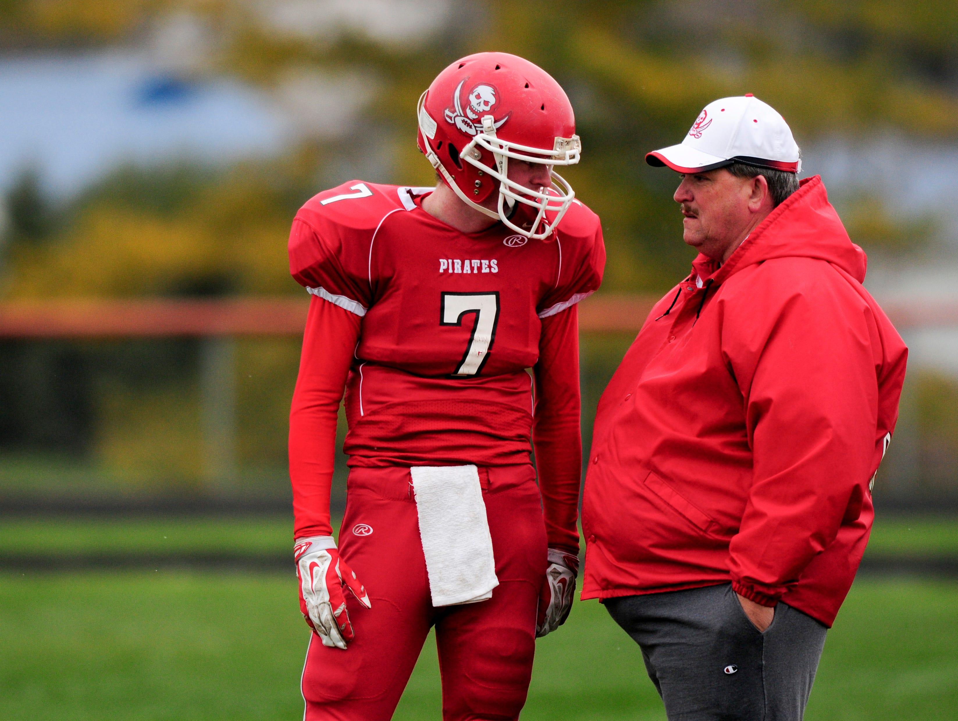 Peck senior Tom Gallagher speaks with coach Rob McDaniel during an 8-man semifinal football game Saturday, Nov. 15, 2014 at Peck High School.