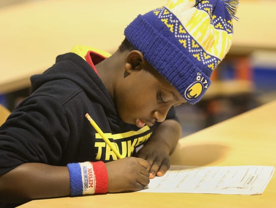 Xavier Johnson-Kiner, 9, does his homework at the Boys