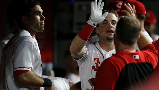 Cincinnati Reds second baseman Scooter Gennett (3) high fives in the dugout after hitting a solo home run in the bottom of the sixth inning of the MLB National League game between the Cincinnati Reds and the Pittsburgh Pirates at Great American Ball Park in downtown Cincinnati on Wednesday, May 23, 2018. The Reds lost 5-4 in 12 innings.