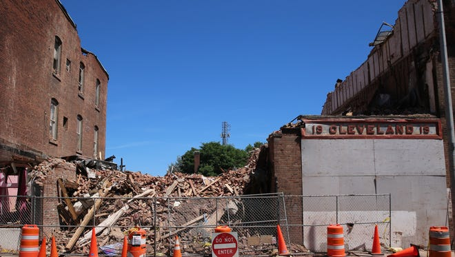 A pile of rubble and a faded building facade sit on Sunday at 17 and 19 Academy St. Cleaning up the debris could take another five weeks, according to Highground Industrial President David Hoehmann.
