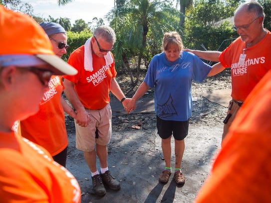 Lori Malone is joined in prayer by volunteers from