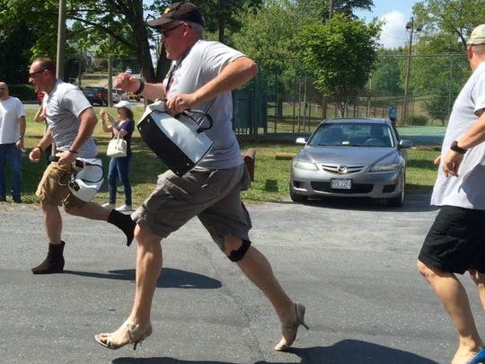 Waynesboro Police Department Sgt. Brian Edwards runs in high heels strapped to his ankles on Saturday to help raise awareness about domestic violence.