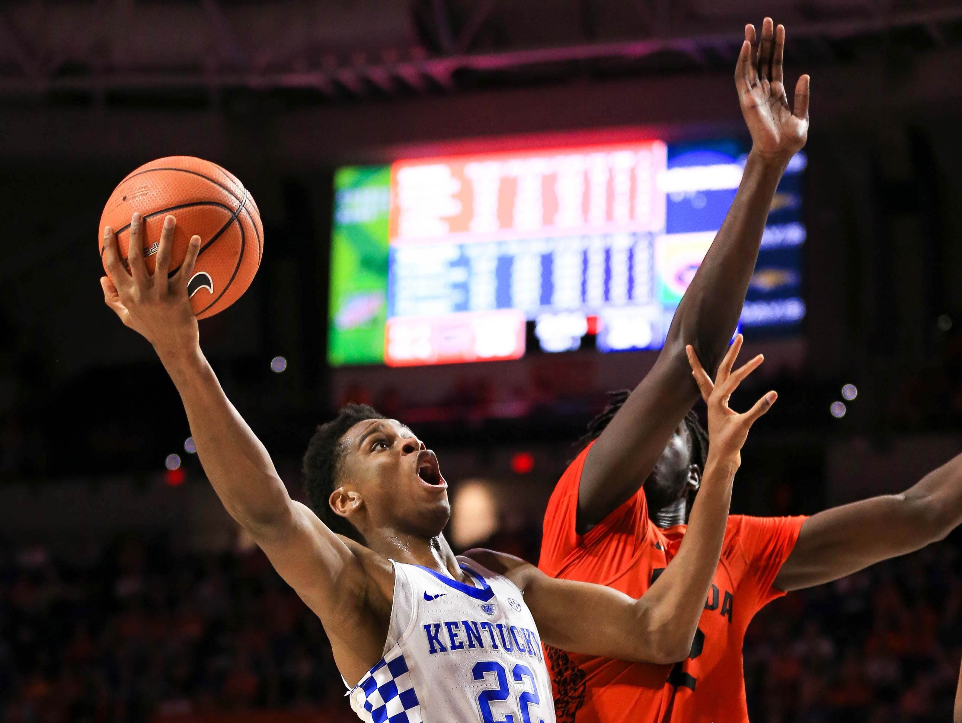 Kentucky Wildcats guard Shai Gilgeous-Alexander (22) makes a layup past Florida Gators center Gorjok Gak (12) during the first half at Exactech Arena at the Stephen C. O'Connell Center in Gainesville, Florida, on Saturday, March 3, 2018.