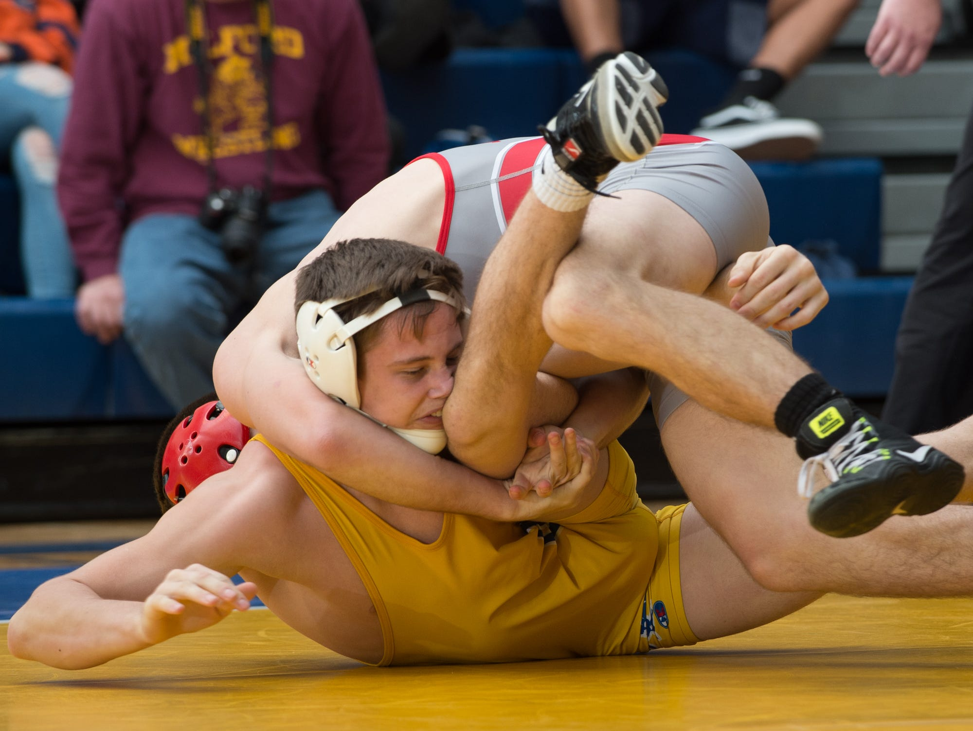 Smyrna's Greg Baum (top) works to roll Caesar Rodney's Jackson Dean on to his back in the 132 pound championship match at the Henlopen Conference wrestling tournament at Sussex Central High School.