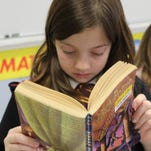 """Evelyn Kuhns of Union reads """"Harry Potter and the Sorcerer's Stone"""" at Villa Madonna Academy. On Drop Everything and Read Day, students and teachers dress as their favorite book characters and at various times, class is interrupted and the class must """"drop everything and read."""""""