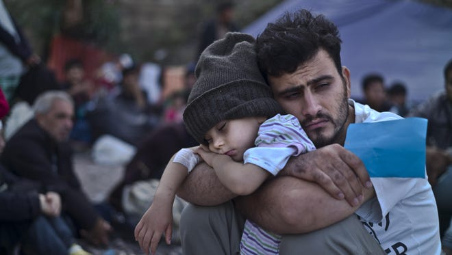 A Syrian refugee child sleeps on his father's arms while waiting at a resting point to board a bus on Sunday, after arriving on a dinghy from the Turkish coast to the northeastern Greek island of Lesbos.
