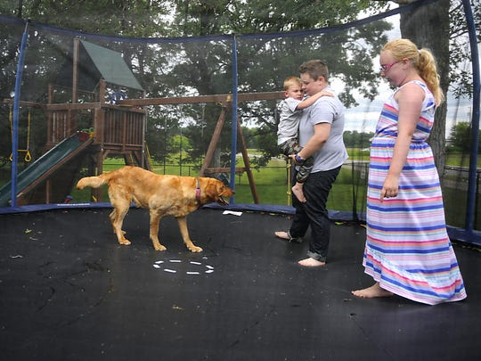 Transgender teen Taelyre Winegar jumps on the trampoline with his little sister Kynnley Winegar and their two dogs while he holds his little brother Jaymeson Miller at their home in Sartell.