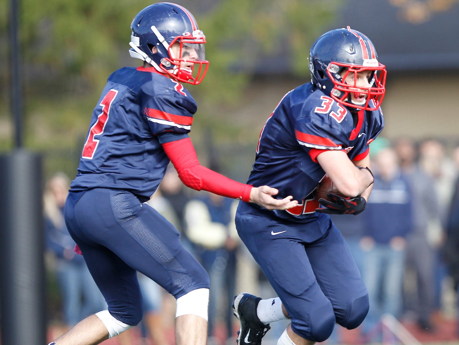 Eastchester quarterback John Arcidiacono (2) hands off to John Guido (33) during their 19-27 loss to Our Lady of Lourdes High School in the class A semi-final football game in Eastchester on Saturday, Oct. 31, 2015.