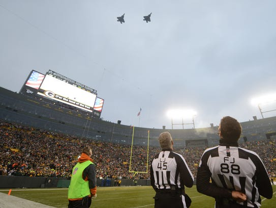 Referees watch as jets fly over during the national