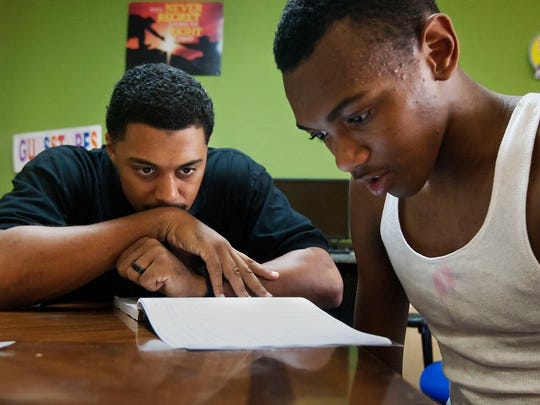 """""""You can do it,"""" Matthew Richard, left, told Noah Jeffries, 14, while helping Noah with his homework recently at The Bridge Youth Center in Fort Myers."""
