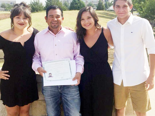 Ricky Delao is shown with his children after the naturalization ceremony. Left to right: Lexis, Ricky, Monica and Colby.