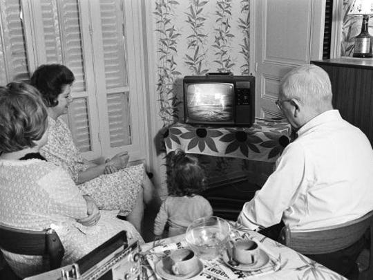 A family watches the American astronaut Neil Armstrong commander of Apollo 11, setting his foot on the moon 21 July 1969. Hundred of millions of television viewers round the world watched this event on television.