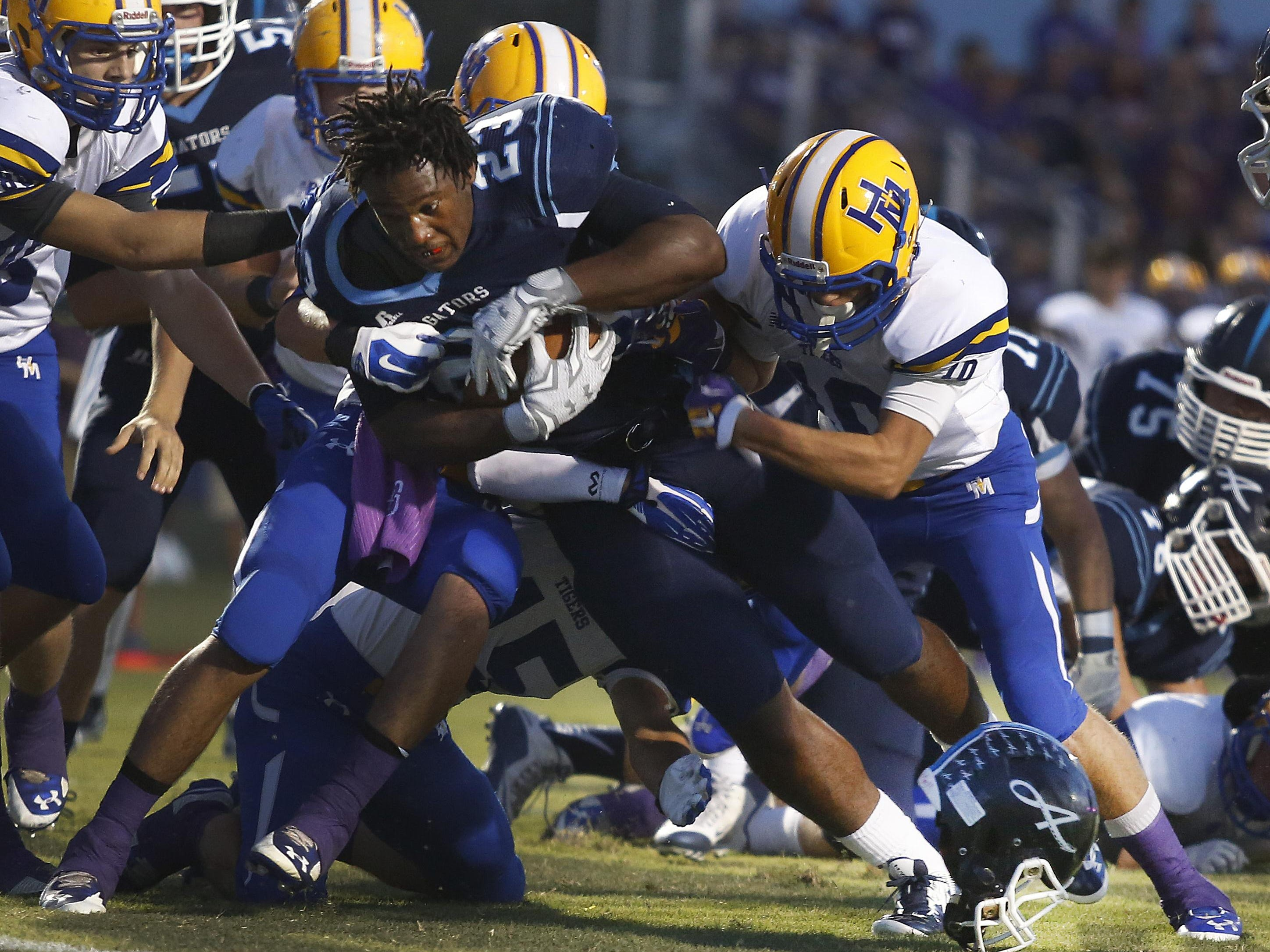 Ascension Episcopal running back Ja'Ceiry Linzer loses his helmet as he drives towards the goal line for the Blue Gators on Friday night.
