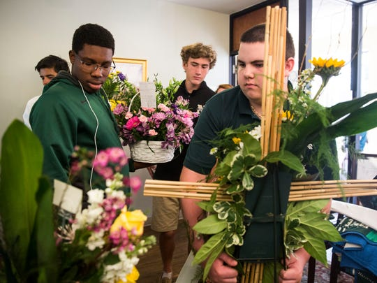 Eddy Garcon, from left, Daniel Kane and William Zonas help carry flowers to the chapel that were sent to the school in remembrance of teacher Shelley Raley at St. John Neumann Catholic High School on Wednesday, May 2, 2018.