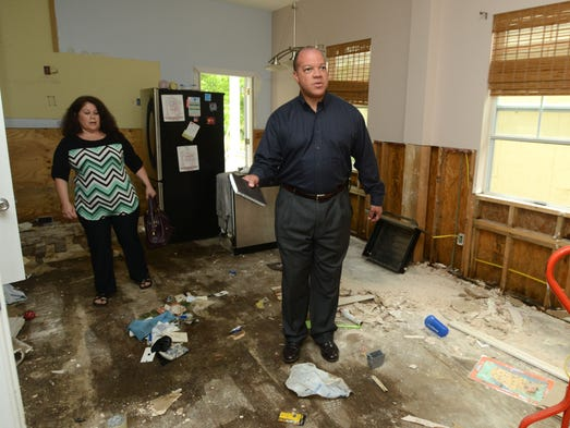 State Rep. Mike Hill tours the home of Patti Daugenti at 816 Guillemard Street on Friday to address concerns of residents in the Long Hollow neighborhood who were swamped with flood water. Many of the residents had questions regarding electrical wiring in their homes after the flood and the condition of a nearby water retention pond that may be the cause of the extreme flooding in the area.